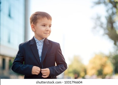 Concept future businessman, president, mayor. Boy in classic dark blue business costume and baby blue shirt walking on pedestrian street, close the jacket button, looking to left.