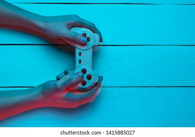 Concept gamer. Nightlife. Leisure. Hand holds gamepad on blue wooden background. Glitch effect