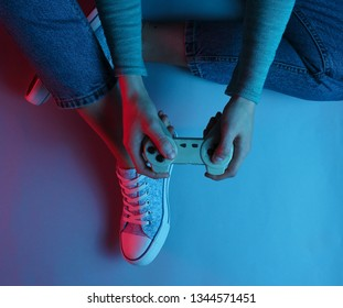 Concept gamer. Nightlife. Leisure. Woman sitting on the floor and holding gamepad. Neon red blue light. Retro wave. Top view