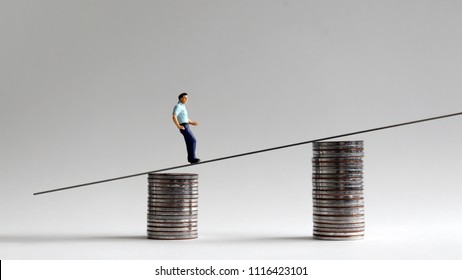 The concept of a gap between wages and inflation. Miniaturepeoplewithtwo stackofcoins.