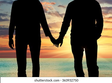 Concept of gay people. Silhouette happy gay men holding hands against the evening sea sunset