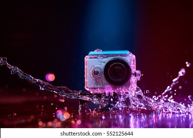 Concept: gear, gadget, action lifestyle, millennial. Vivid colorful shot of action camera in waterproof case splashed with water. Time freeze.