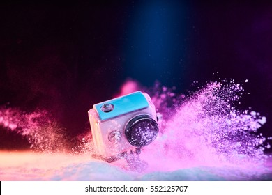 Concept: gear, gadget, action lifestyle, millennial. Vivid colorful shot of action camera in waterproof case fall dropped in powder sand. Time freeze.