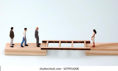 Miniaturemenandaminiaturewomanstandingonwoodenblockswithladdersbetweenthem. The concept of gender discrimination.