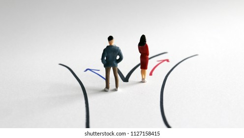 The concept of gender division. A miniature man and a miniature woman standing on two separate paths.