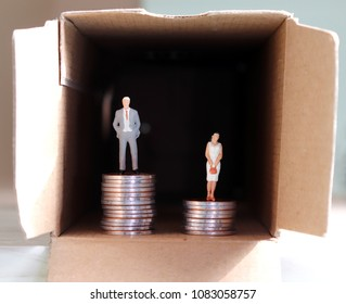 The concept of gender employment and wage differential. Miniaturemanandwomanonpileofcoins.