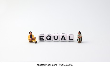 The concept of gender equality. A miniature man and a miniature woman sitting next to the EQUAL text cube.