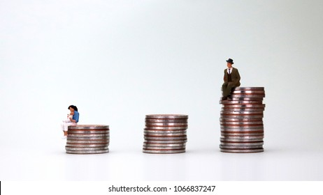 The concept of gender inequality. A miniature man sitting on a pile of coins and a miniature woman holding a baby sitting on a pile of coins.