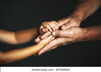 The concept of generations. Hand of a child and an elderly person
