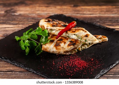 The concept of Georgian cuisine. Baked pita with suluguni cheese and cilantro. Serving dishes on a black stone slate. On a wooden background. copy space
