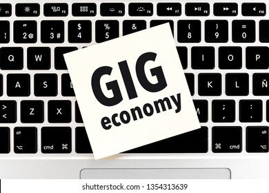 Concept of GIG ECONOMY with a close up adhesive note on keyboard notebook, laptop.