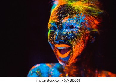 Concept. The girl smiles. Portrait of a girl painted in fluorescent powder.