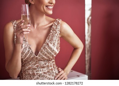 Concept of girls party. Cropped head portrait of model posing happy woman in elegant festal dress holding champagne glass in one hand and other put on waist