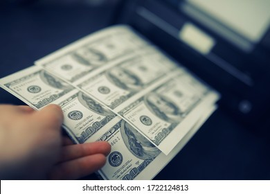 The concept of global economic crisis. Illegal production of US dollars. Print money underground. Printing hundred dollar bills by a criminal.