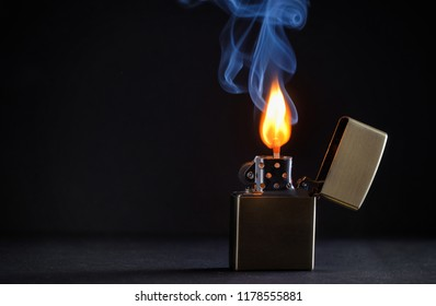 Concept golden metal lighter and smoke
