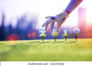 concept of golf ball invitation on incoming year 2019, prepare by hand of woman on tee off,  ready to hit away the new year success on fairway, Happy new year and merry christmas on golf course