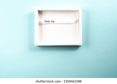 """Concept of good job or searching new job. White opened box framing the text """"good job"""" on blue background"""