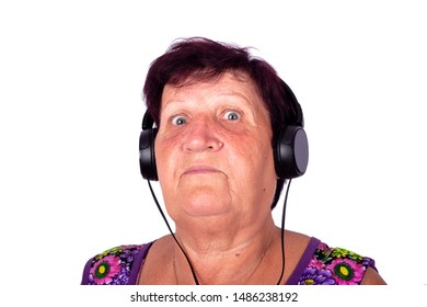 concept: grandma listens to music, ,grandmother in headphones is shocked of modern music with wide eyes  isolated close-up