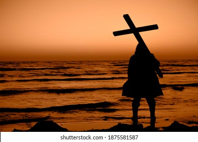 concept of great geographical discoveries, christian cross and lonely man on a sea shore in the dark