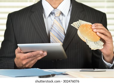 Concept for greedy corporate executives, Businessman is eating a burger stuffed with money and browsing on a tablet computer in his office