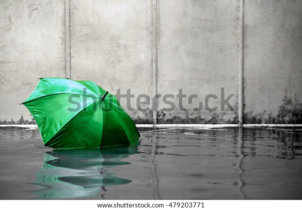 Concept of green umbrella floating on flooded street and waiting for help me after the rain.