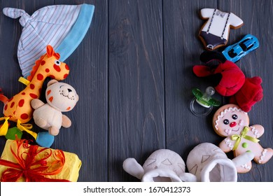 Concept for greeting card to a newborn baby with toys, hat on a dark gray wooden background with space for copy space. View from above