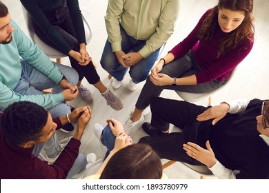 Concept of group therapy meeting, talking about and dealing with psychological problems, getting help and support. High angle of diverse people sitting in circle listening to man sharing his concerns