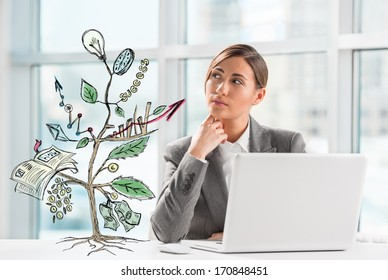 Concept of Growing company with sketch of a plant with business symbols and businesswoman working on laptop