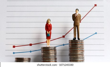 Miniaturepeoplestandingonapileofcoinsinfrontofagraph. The concept of the growing income gap in the profession.