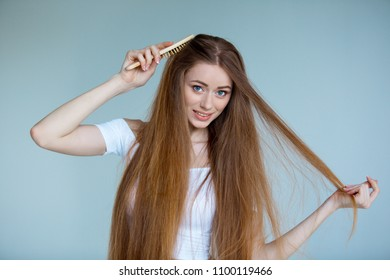 Concept of hair loss. Close up portrait of unhappy sad stressed young woman with long dry brown hair, isolated on grey background.