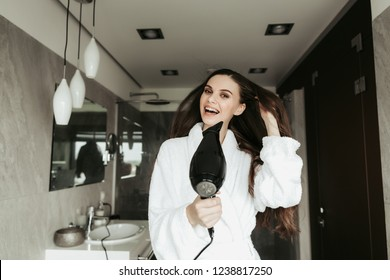 Concept of haircare and treatment after shower. Waist up portrait of cheerful brunette lady drying her long hair with blowdryer at home bathroom interior