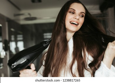 Concept of haircare and treatment after shower. Close up portrait of cheerful brunette lady drying her long hair with blowdryer at home bathroom interior