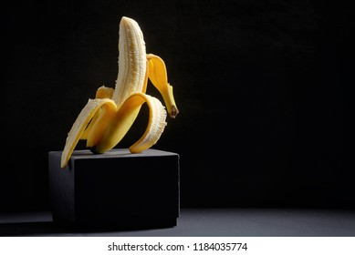 Concept with Half peeled banana on black background
