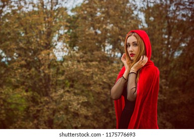 Concept of Halloween. Beautiful and simple costume of little red hood. Mysterious hooded lady figure . Girl in red raincoat. Cosplay Fairy Tale Little Red Riding Hood