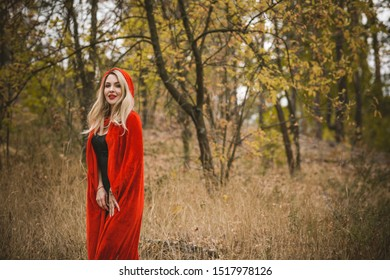Concept of Halloween. Beautiful and simple costume of little red hood. Mysterious hooded figure in misty forest. Girl in red raincoat. Cosplay Fairy Tale Little Red Riding Hood