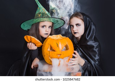 The concept of Halloween, funny face. Funny child girl in pumpkin costume for Halloween with pumpkins and holiday attributes. Children's party. Cute little witch dressed in hat with a pumpkin.