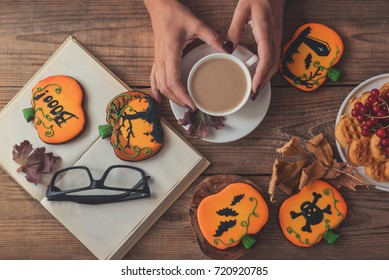 concept halloween, stylistic cookies on the table. women's hands, a cup of coffee, a book and glasses