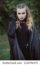 The concept of Halloween. A witch in black robes and green lips among the forest. Witchcraft and magic. Photo for your design.
