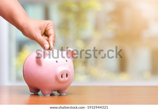 Concept hand putting money coin into piggy bank saving money for future plan and retirement fund, Business or finance saving show putting coin saving and investment money  retro vintage color tone.
