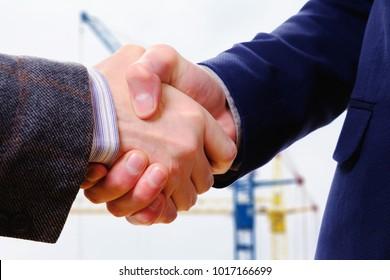 Concept handshake, contract conclusion businessman builder, looking construction city site with cranes