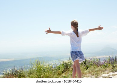 Concept of happiness. Cute happy  child in white blouse on a rock with raised hands and looking to a valley below