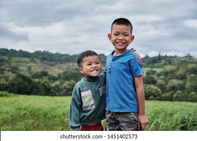 Concept happy asian kids lifestyle. Older brother hugs  younger brother ,by the neck, shoulders with big smile on green mountain background in a countryside