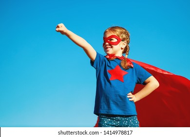 concept happy child superhero hero in red cloak at sunset in nature