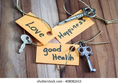 concept for a happy life using an old decorative key and a hand written tag attached by a golden cord