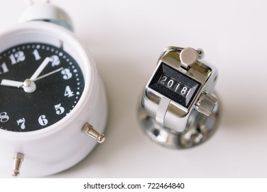 Concept of Happy New Year 2018 celebration. Number Hand Tally Counter stop at 2018 and alarm clock on white table with copy space.