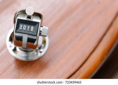 Concept of Happy New Year 2018 celebration. Number Hand Tally Counter stop at 2018 on white wooden table with copy space.