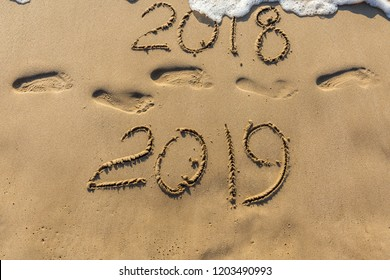 Concept of Happy New Year 2019 is coming and leaving year of 2018. Text on the sea beach and footprints on the sand. Wave water covering digits inscription. Meet at a tropical resort in Thailand.