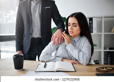 Concept harassment. Afraid young woman sit at table. Harrasment goes out of her boss. He keep hand on her shoulder. Guy wat to have sex with model.