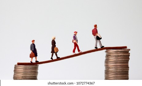 Miniaturepeoplewalkingfromlowtohighpileofcoins. The concept of hard work and a gap between the rich and poor.