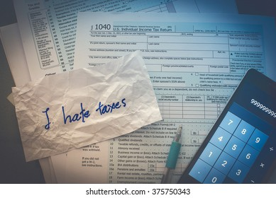 "Concept Hate taxes. Tax form with calculator, pen and the text ""I hate taxes"" on the crumpled paper."